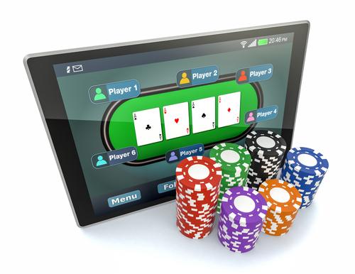 tablette informatique avec une application de poker en ligne ainsi qu'une multitude de jetons de casino posés à côté
