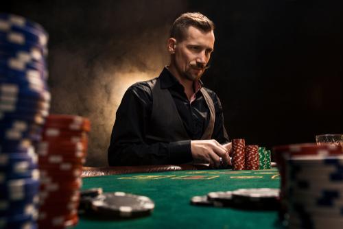 jeune homme assis à une table de poker avec des cartes et des jetons