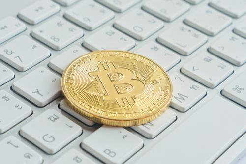 Illustration d'un bitcoin de couleur doré posé sur un clavier d'ordinateur