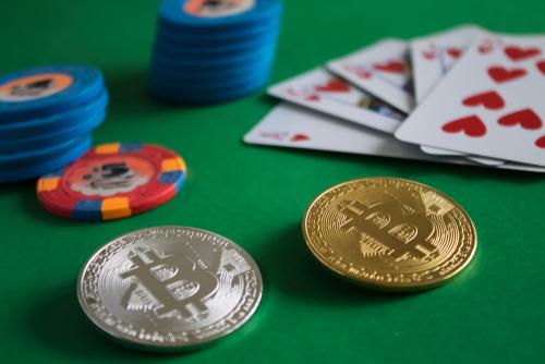 deux bitcoin posés sur une table de jeu avec des jetons de casino et un jeu de cartes