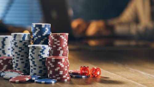 plusieurs piles de jetons de casino posés sur une table avec des dés rouge à côté
